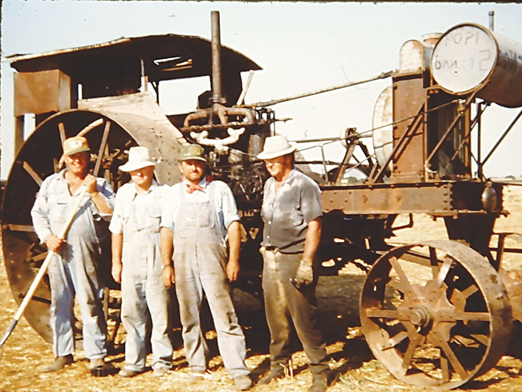 Strnad brothers stand in front of a rare, 100-year-old Minneapolis gas tractor.
