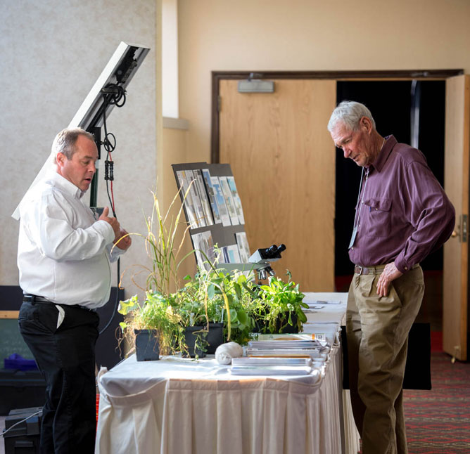 Dale Strickler, Star Seed, and Herb Bartel, KFU board, discuss forages.