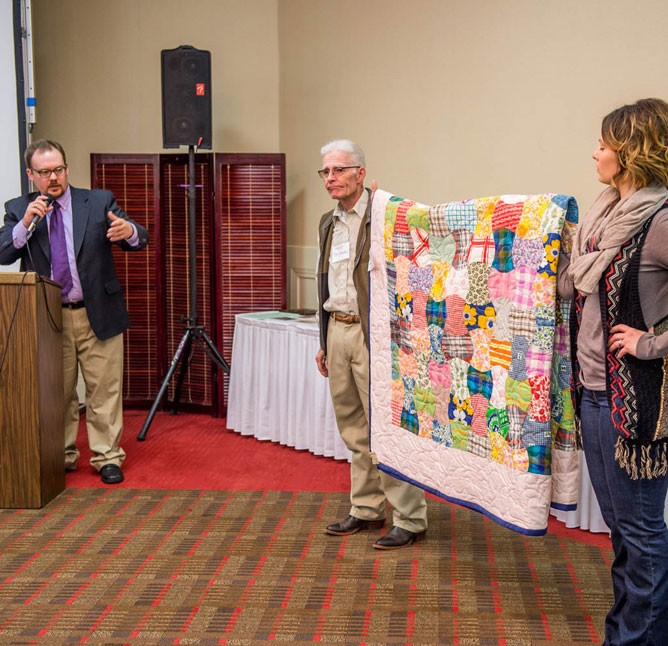 Nick Levendofsky describes a quilt donated by Becky Craig held by Tim Olmstead and Kristen Swanson.