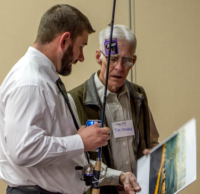 Ty Racette, MRA agent from Larned, and Tim Olmstead admire a photo donated by Tom Parker to the 2015 KFUF auction.