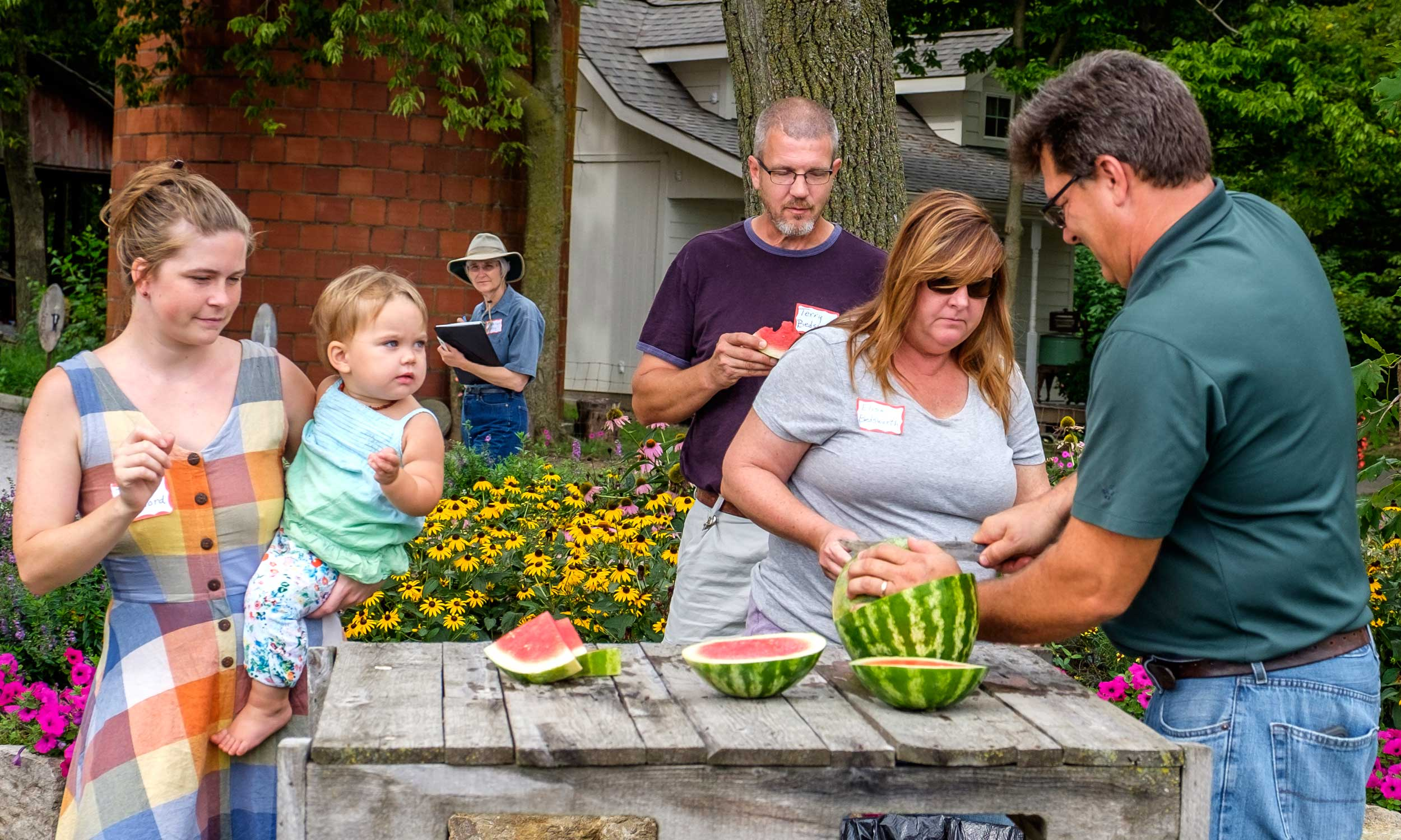Jay Schwinn of Schwinn Produce Farm and Barn, slices watermelon for those on last month