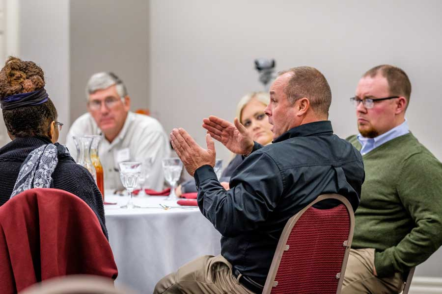 Dale Strickler, farmer and rancher from Jamestown, poses a question to NFU's Rob Larew.