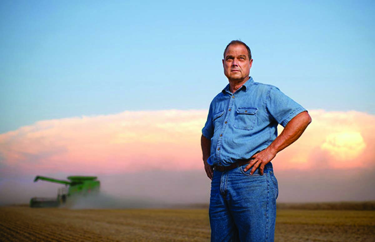 Tom Giessel in the field with combine in background