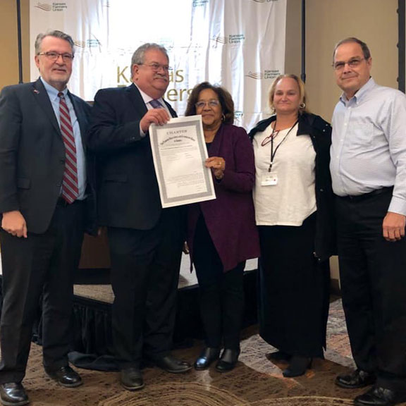 The new Creative Grower Connectionschapter was chartered at this year's convention banquet. From left, Lt. Governor Lynn Rogers, KFU President Donn Teske, Chapter President Donna P McClish, Chapter Secretary Janice Mingo, and National Farmers Union Historian Tom Giessel.